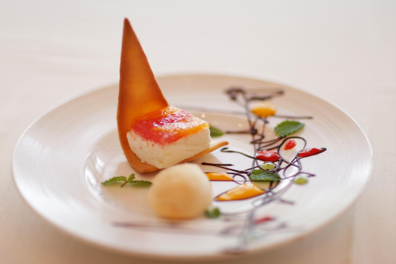 【デザート】クリームチーズのムースで作った宝石箱 フランス産クリームチーズでムースを作り、2色のグレープフルーツと オレンジをムースにのせ、サブレ生地を添えて宝箱のように 幾何学模様のパレットの空白を思い出で埋めて…   愛媛県西条市の結婚式場ベルフォーレ西条